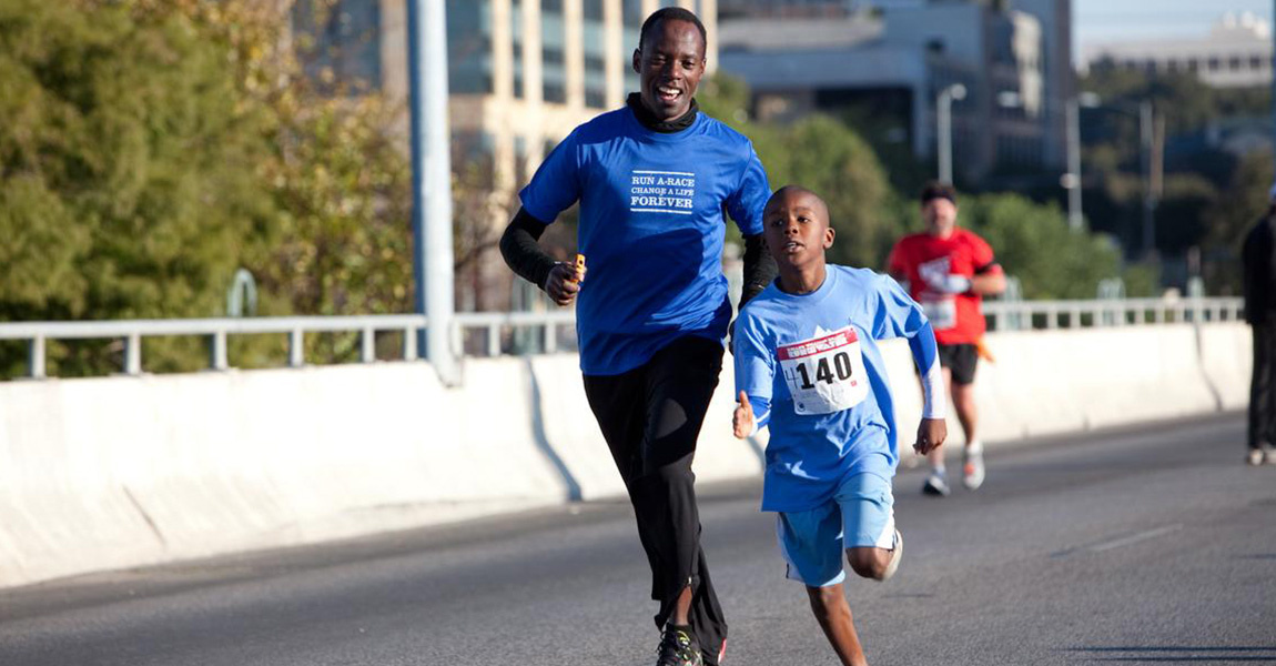 Gilbert Tuhabonye running with a child at Run for the Water